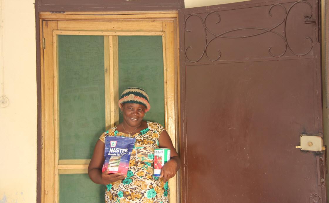 A Smallholder Farmers Alliance (SFA) member farmer stands outside her  store 12ddac0749